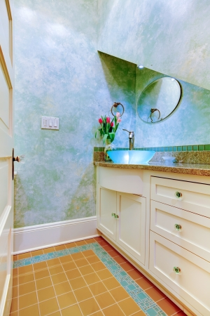powder room: Small beautiful blue bathroom, powder room with blue sink and white cabinets.