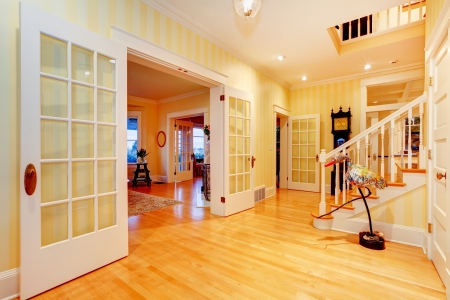 Golden bright yellow luxury home main hallway, entrance with staircase and open doors to living room. photo