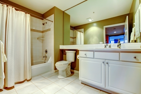 Green and white bathroom with sink and tub with curtain. photo