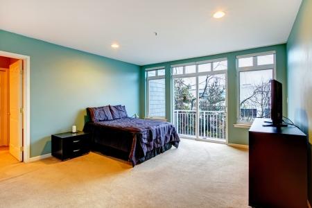 balcony door: Amplio dormitorio con cama de color azul brillante p�rpura y la puerta del balc�n. Foto de archivo