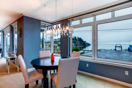 dining table and chairs: City apartment dining room with round small table and blue walls.