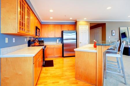 City apartment orange wood kitchen with bar stools.