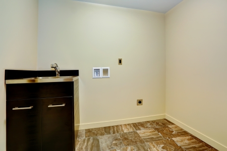Empty new laundry room with sink and cabinet.