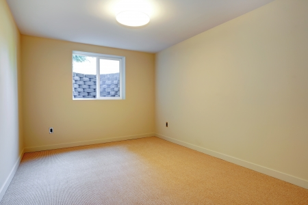 Empty room with beige carpet and small basement window. Stock Photo - 20993018