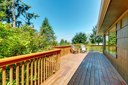 Large Deck, terrace with wood railings and green landscape.