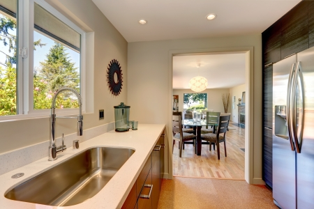 sink: Modern small new kitchen with large sink and white countertops.