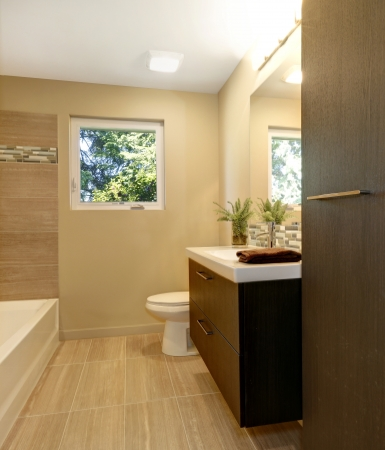 Beige modern new bathroom with brown wood cabinets and tub. Stock Photo