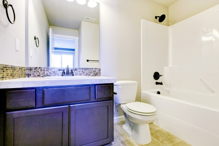 New home bathroom  interior with shower and bath combination, wood cabinet and toilet. Stock Photo - 21728639