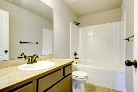 New home bathroom  interior with shower and bath combination, wood cabinet and toilet. Stock Photo - 21728641