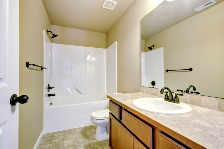 New home bathroom  interior with shower and bath combination, wood cabinet and toilet. Stock Photo - 21728643