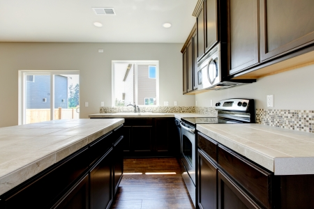 New home kitchen interior with dark brown cabinets and hardwood floors. Stock Photo - 21728648