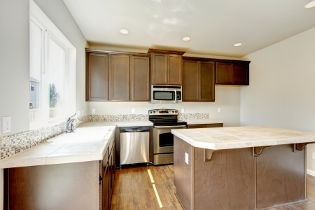 New home kitchen interior with dark brown cabinets and hardwood floors. Stock Photo - 21728649