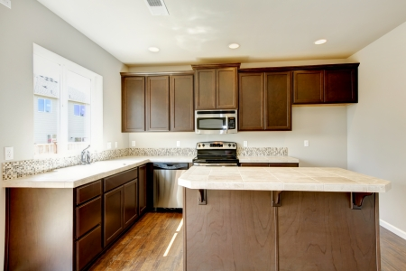 New home kitchen interior with dark brown cabinets and hardwood floors. Stock Photo - 21728650
