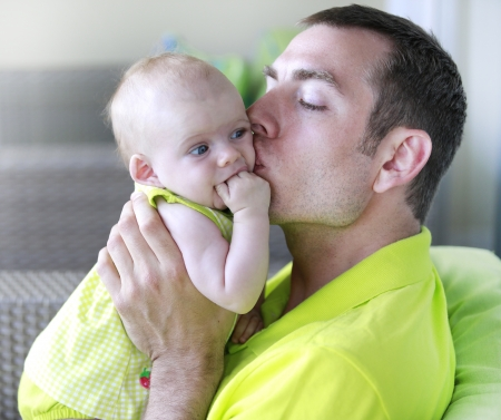 Young father is kissing baby girl. baby girl. Stock Photo - 21573736
