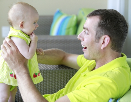 Father and little baby girl are playing together wearing neon green  Stock Photo - 21728935