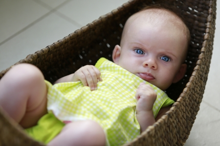 Beautiful three month old baby girl with blue eyes in the basket Stock Photo - 21728947