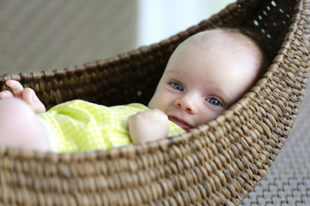 Beautiful three month old baby girl with blue eyes in the basket  Stock Photo - 21728958