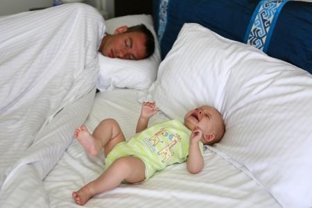 Sleepless parenthood  Father is trying to sleep near awake and crying baby Stock Photo - 21728963