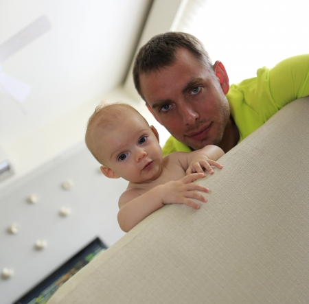 Little baby and young father are watching sport on TV in modern apartment  Stock Photo - 21728968