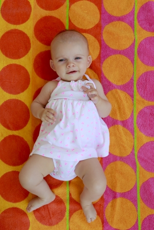Baby girl of four months laying on the beach towel of red and orange circles Stock Photo - 21728973