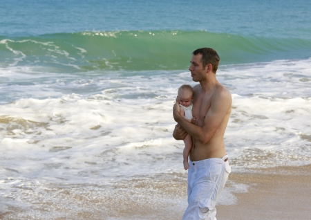 Young father holding baby on the beach near ocean with lighthouse  Beautiful vacation time for family  Stock Photo - 21729019