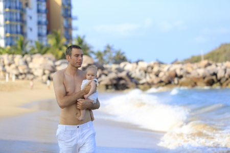 Young father holding baby on the beach near ocean with lighthouse  Beautiful vacation time for family Stock Photo - 21729087