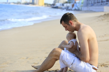 Young father holding baby on the beach near ocean with lighthouse. Beautiful vacation time for family. Stock Photo - 21573772