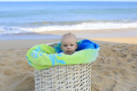 Beach baby girl in the white basket with green towel  Tropical vacation Stock Photo - 21729099