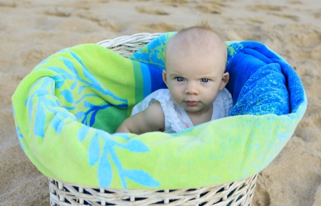 Beach baby girl in the white basket with green towel  Tropical vacation  Stock Photo - 21729100