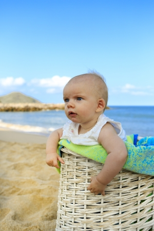 Beach baby girl in the white basket with green towel  Tropical vacation  Stock Photo - 21729102