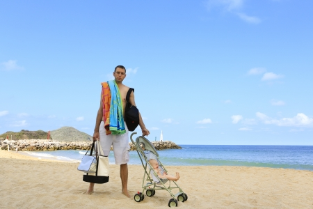 Young father is dragging stroller with little baby on the sandy beach near ocean. Stock Photo - 21559010