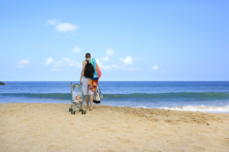 Hands full during vacation with baby  Young father is dragging stroller with little baby on the sandy beach near ocean Stock Photo - 21717752