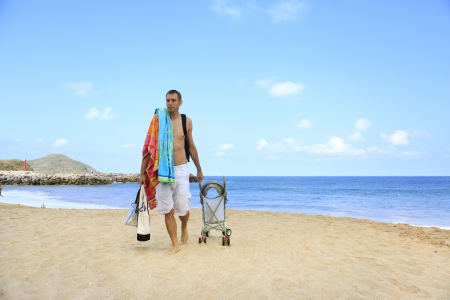Young father is dragging stroller with little baby on the sandy beach near ocean. Stock Photo - 21573784