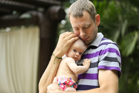 vacaton: Three months old baby girl is held by her daddy near pool during vacation