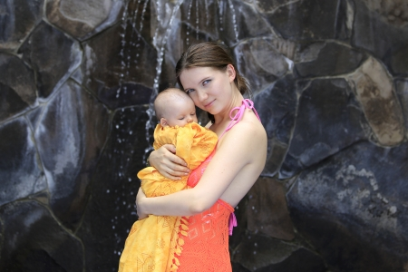Beautiful young mother is holding baby girl outside near fountain rock wall. Stock Photo - 21573791