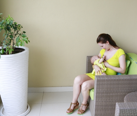 Young beautiful mother is breastfeeding baby. Nursing time on the balcony. Stock Photo - 21573792