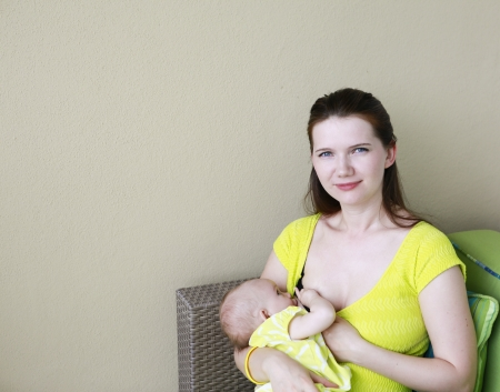 Young beautiful mother is breastfeeding baby. Nursing time on the balcony. Stock Photo - 21573836