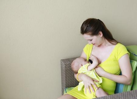 cadeira: Mãe bela e jovem está amamentando o bebê. Tempo de enfermagem na varanda.