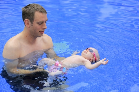 three months old: Small baby girl is swimming in the pool with daddy for the first time  Three months old baby  Stock Photo