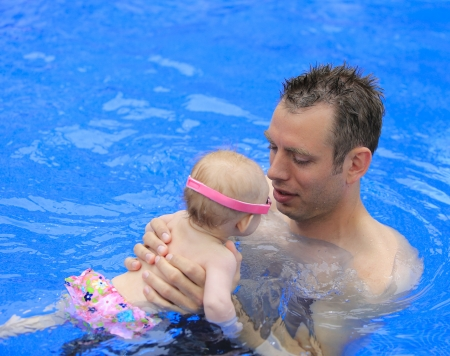 Small baby girl is swimming in the pool with daddy for the first time  Three months old baby  Stock Photo - 21729120