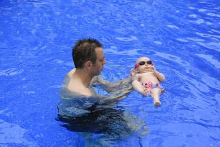 Small baby girl is swimming in the pool with daddy for the first time  Three months old baby  photo
