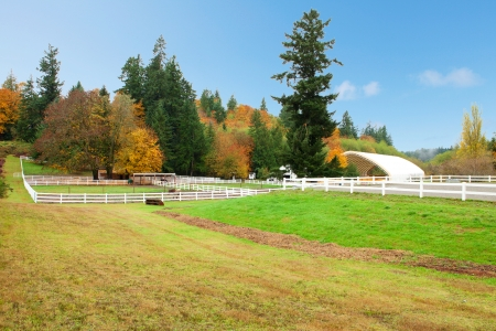 Northwest horse rach with fall changing leaves and white fence. Stock Photo - 23131498