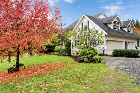 Northwest horse ranch white house with fall changing leaves and white fence. Stock Photo