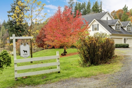 Northwest horse ranch white house with fall changing leaves and white fence. Stock Photo - 23131504