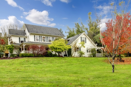 front or back yard: Northwest horse ranch white house with fall changing leaves and white fence. Stock Photo