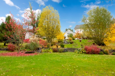 old red barn: Northwest horse ranch white house with fall changing leaves and white fence. Stock Photo