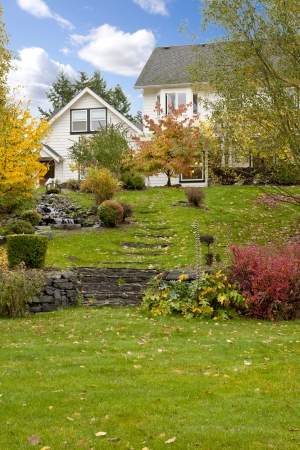 gig harbor: Northwest horse ranch white house with fall changing leaves and white fence. Stock Photo