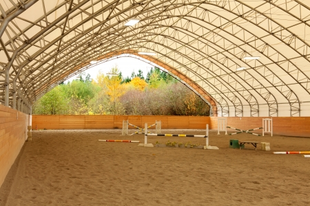 Covered open horse arena with sand and white ceiling. Stock Photo - 22285350