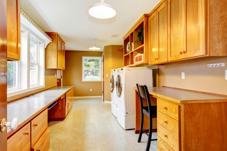 Large bright laundry room with desk and lots of storage.