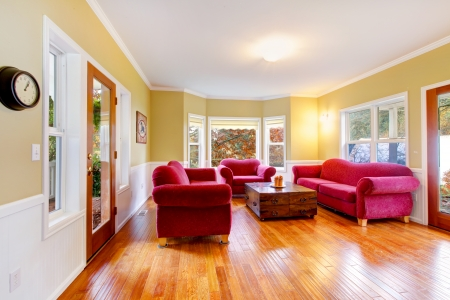 Large living room with hardwood and pink red sofas. photo